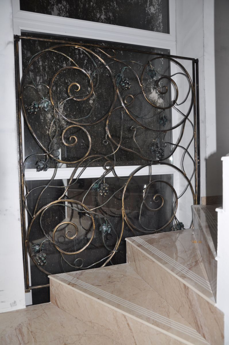 Лестница с прямыми и забежными ступенями из керамогранита под мрамор, аранжированная коваными металлическими перилами