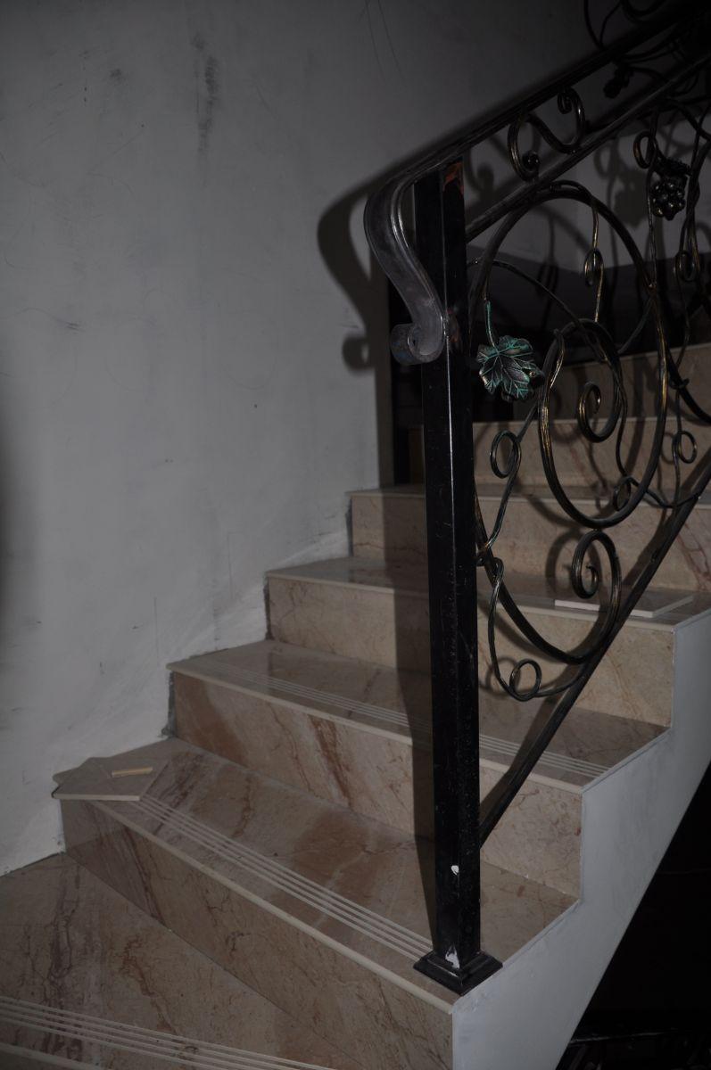 Готовая лестница в загородном доме, ступени которой покрыты керамогранитом под мрамор и коваными металлическими перилами