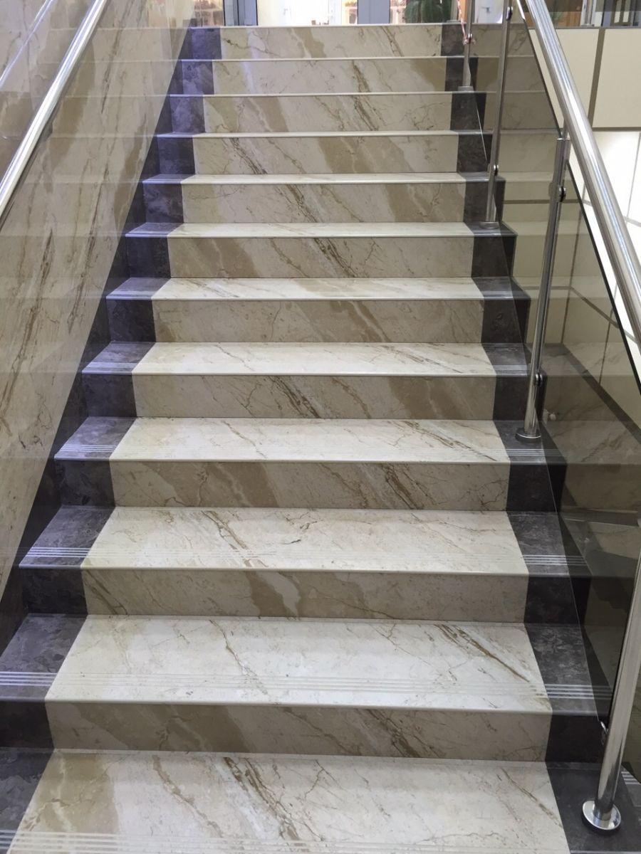 Подъемная часть лестницы на второй этаж с прямыми ступенями из керамогранита под мрамор методом ковровой дорожки
