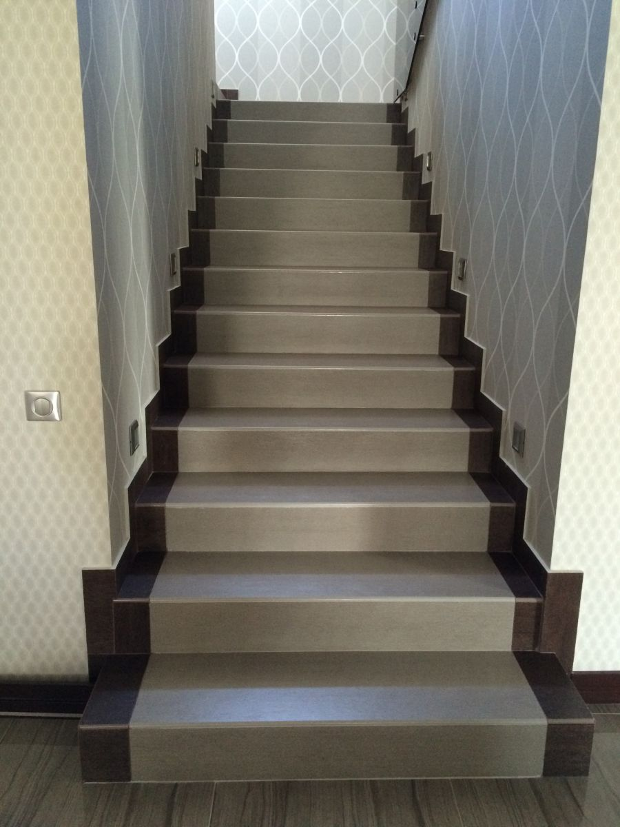 фронтальное фото лестницы на второй этаж со ступенями из керамогранита под дерево большого размера
