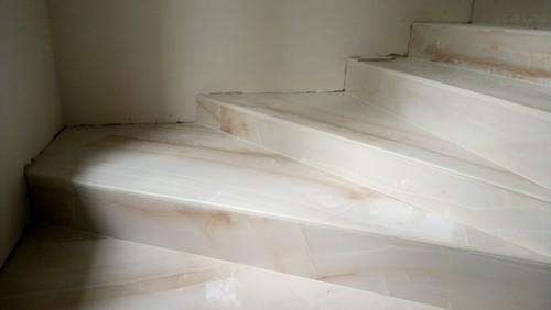 Лестница на второй этаж загородного дома, облицованная ступенями из керамогранита под оникс 1200х300х10 мм. Фото лестницы