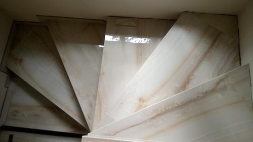 Забежные ступени поворотной лестницы в доме из керамогранита под камень
